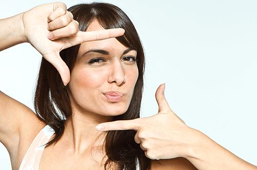 Frau mit schönen Nägeln verzieht den Mund